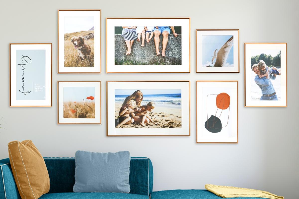 Acht Bilder hängen an der Fotowand über einem Sofa im Wohnzimmer