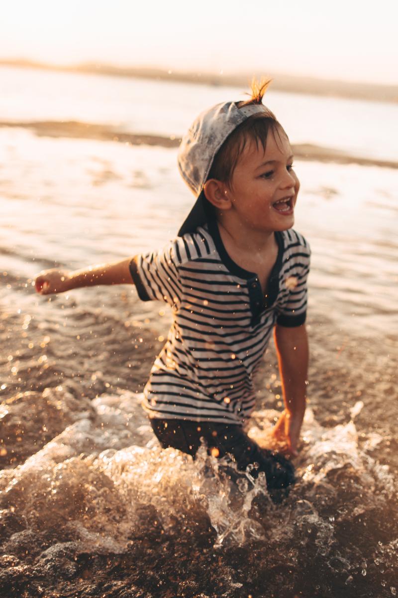 Lachender Junge rennt im T-Shirt durchs Wasser