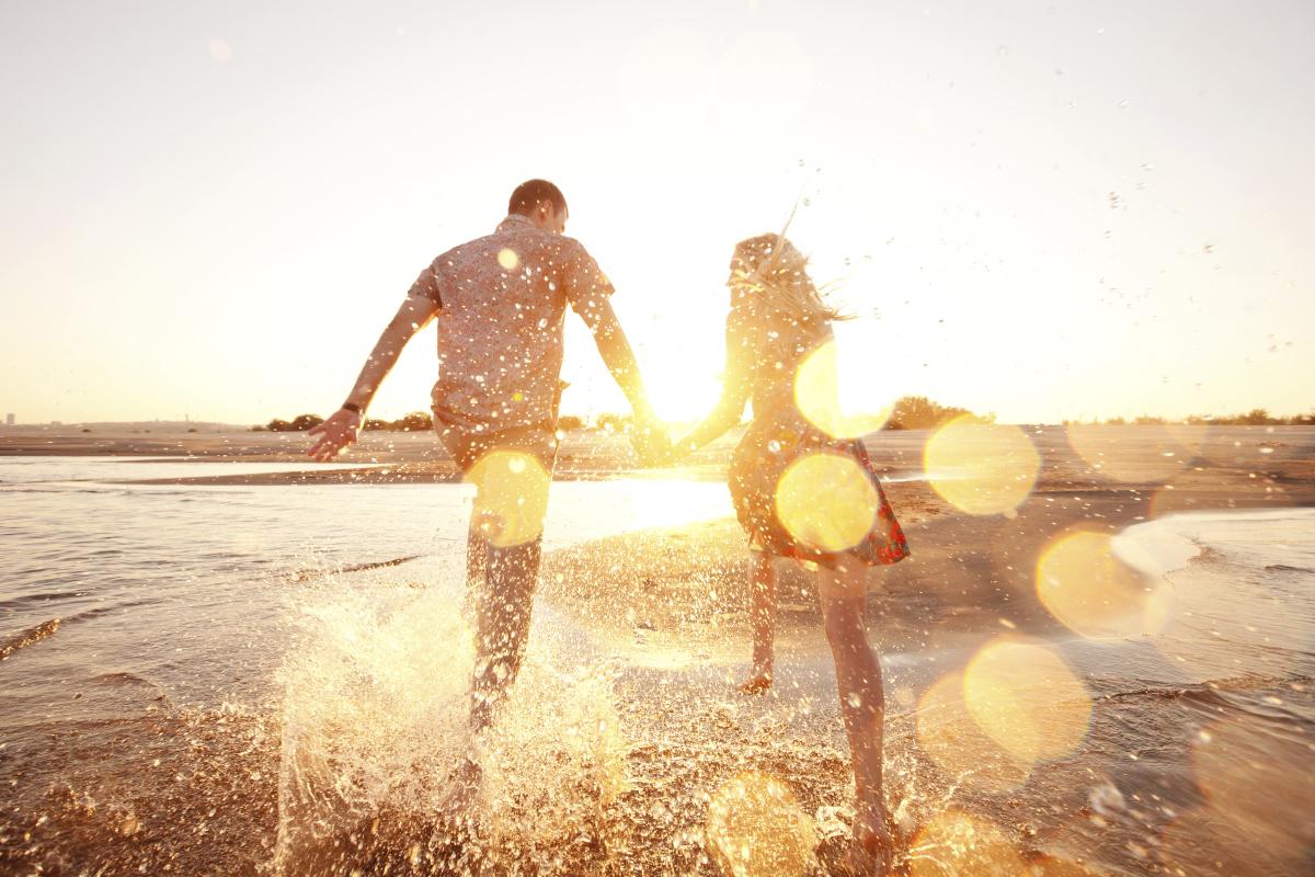 Paar läuft händchenhaltend am Strand mit dem Rücken zur Kamera bei Gegenlicht, sodass das Wasser spritzt und Reflexe auf der Linse entstehen.