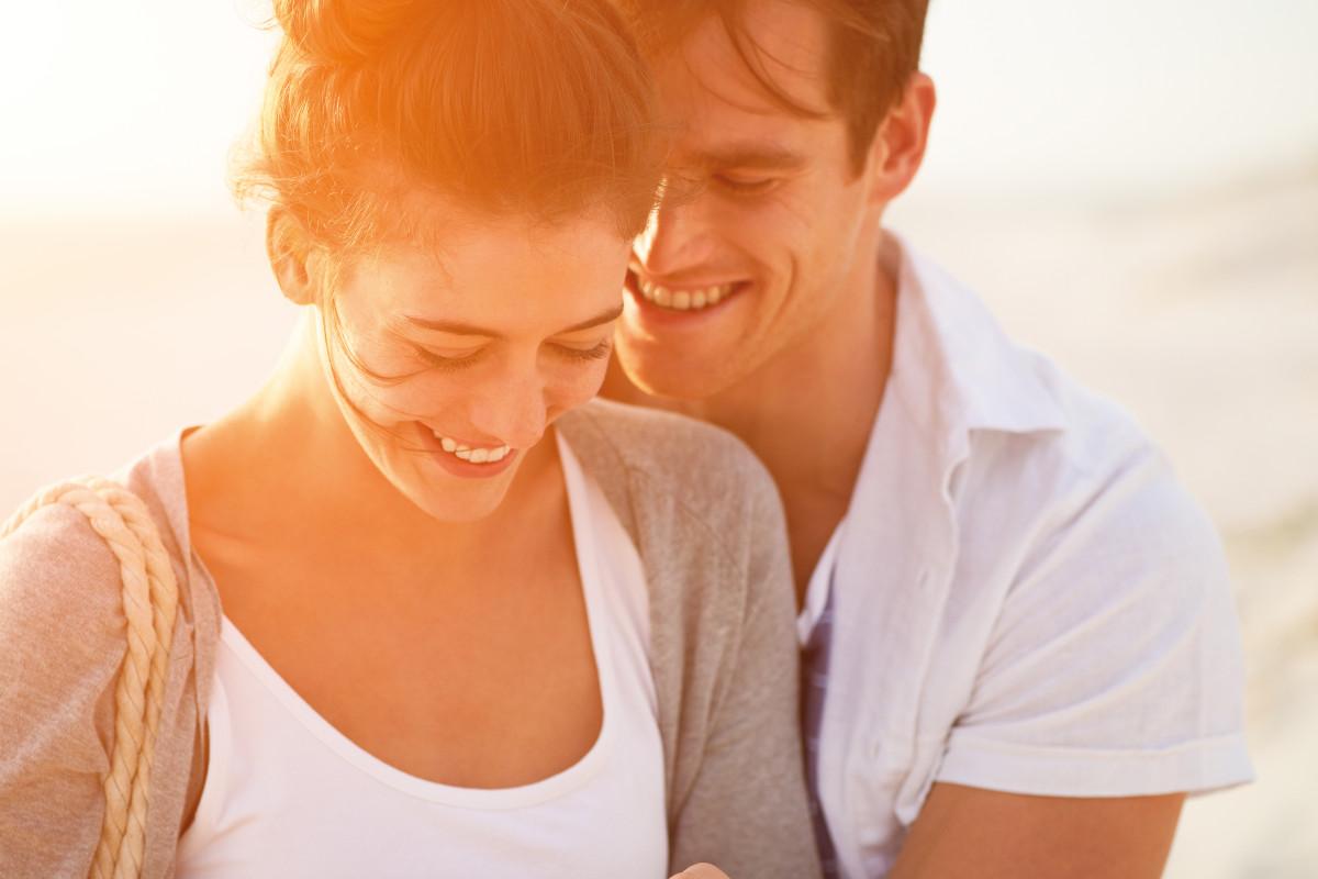 Lachendes Paar am Strand bei Sonnenuntergang