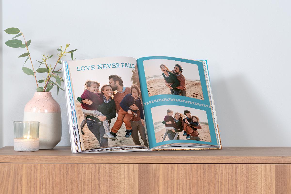 Pixum Fotobuch mit Familienbilder vom Urlaub liegt auf der Komode