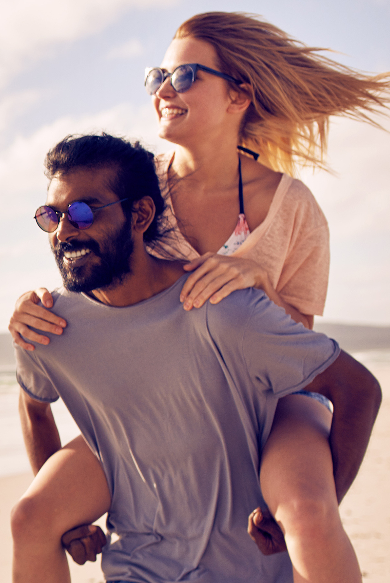 Paar mit Sonnenbrille am Strand, er trägt sie Huckepack