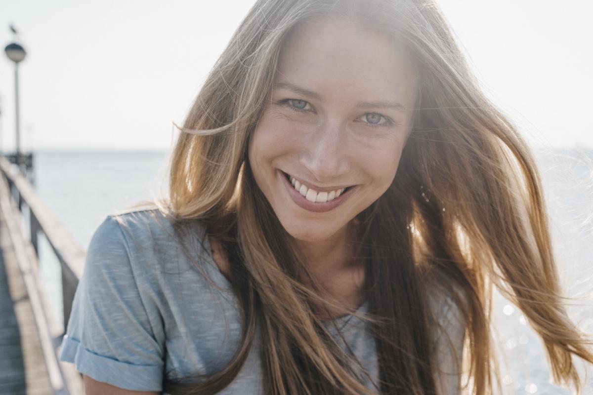 Frau lächelt in die Kamera bei Gegenlicht am Wasser