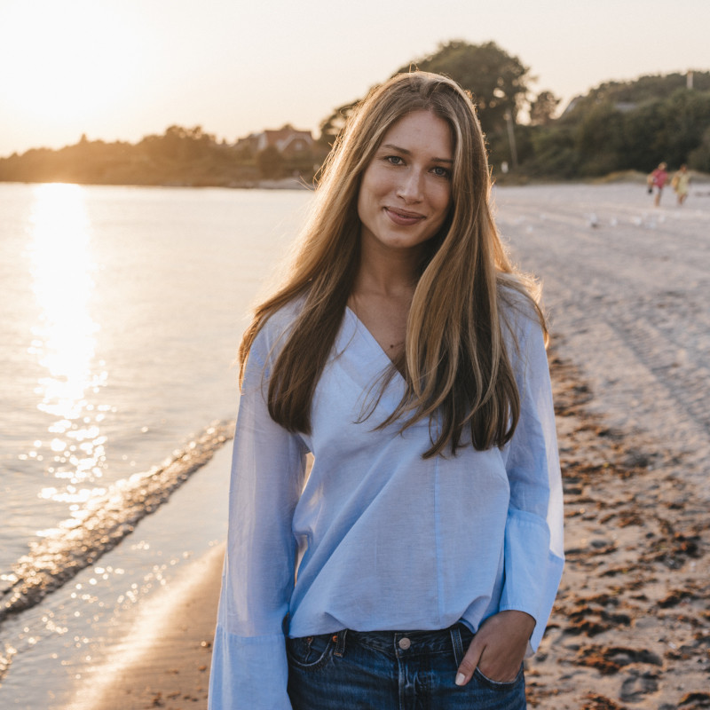 Frau lächelt in die Kamera bei Sonnenuntergang am Strand