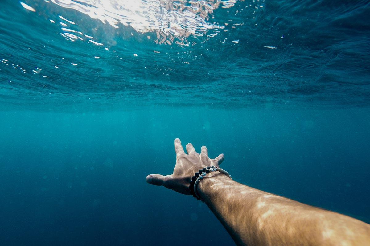 Unterwasserfoto eines ausgestreckten Arms in Richtung Wasseroberfläche