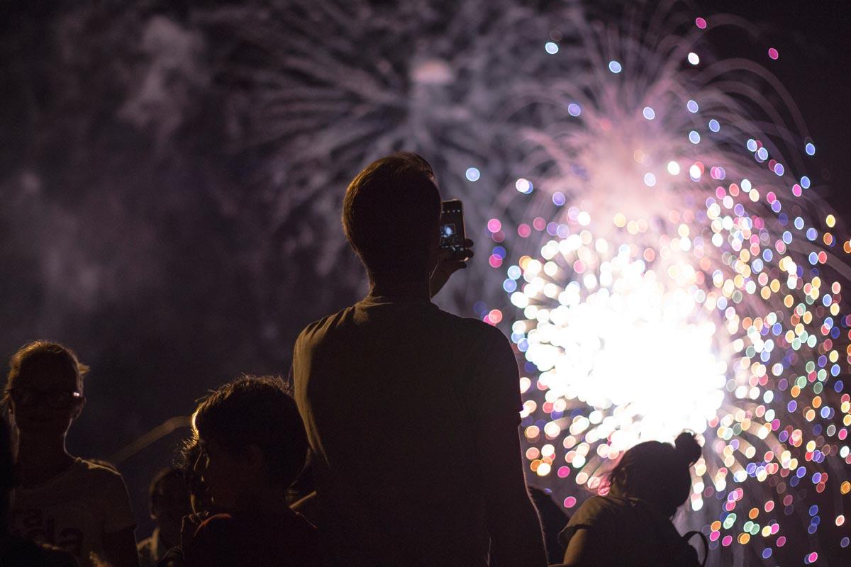 Ein Mann fotografiert ein Feuerwerk mit dem Smartphone.