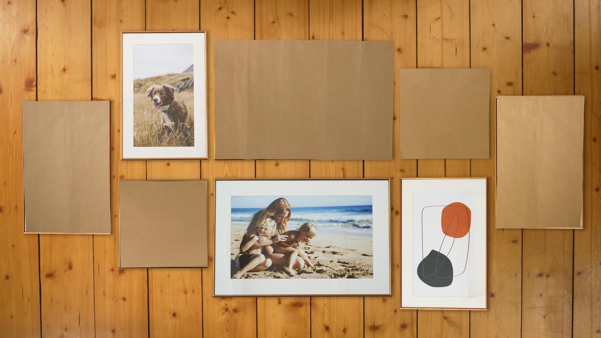 Am Boden werden zunächst die Bilder für die Fotowand angeordnet und mit Pappe entsprechende Schablonen angefertigt