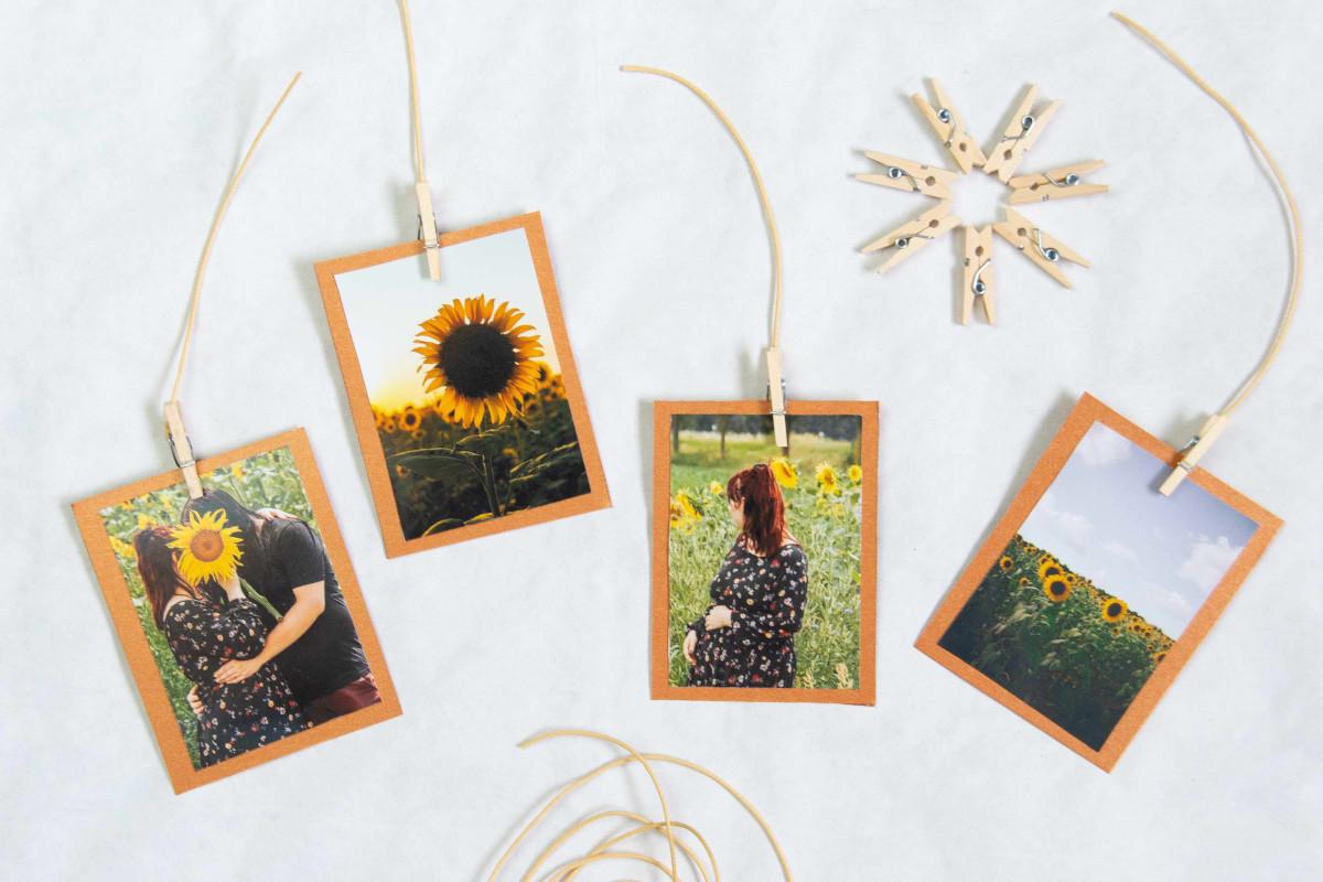 Pixum Fotoabzüge mit Klamern auf zugeschnittenem Pappkarton fixieren.