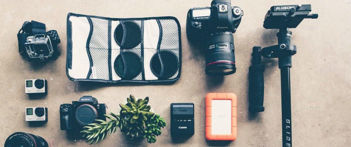 Verschiedene Elemente einer Kameraausrüstung liegen auf dem Boden