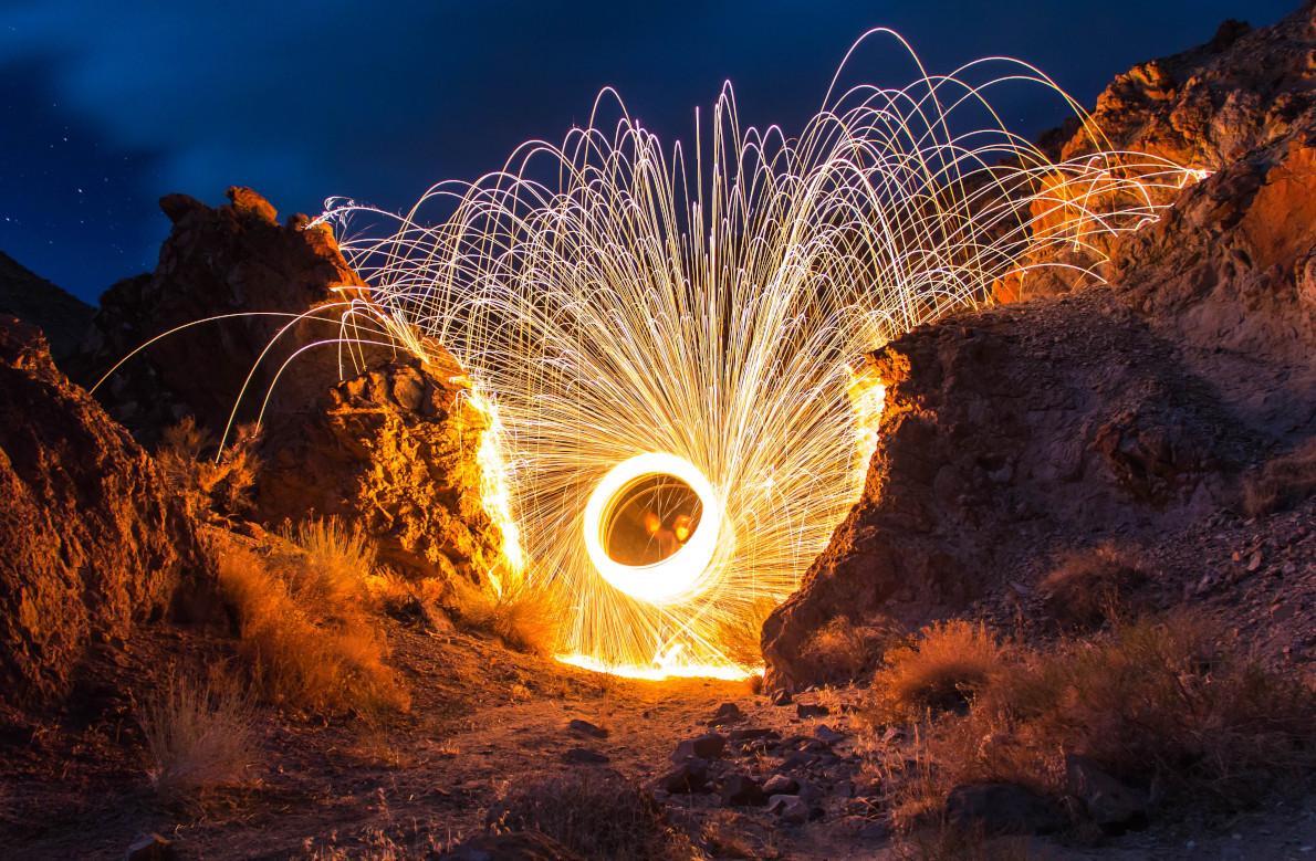 Lichtkreis mit sprühenden Funken zwischen Felsen