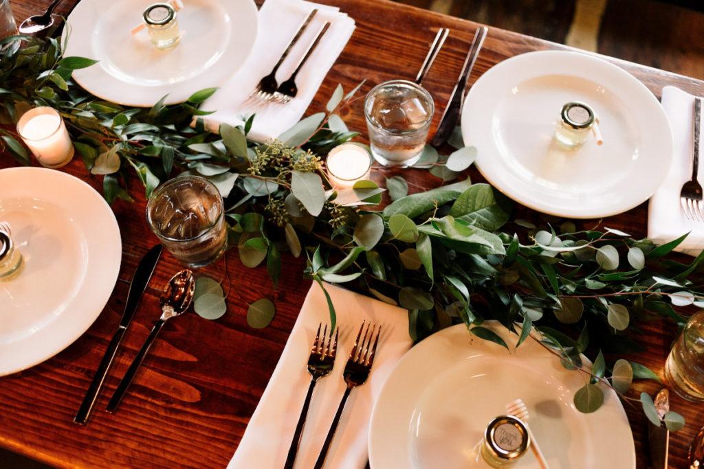 Tischdeko einer Hochzeit mit Eukalyptus und Kerzen