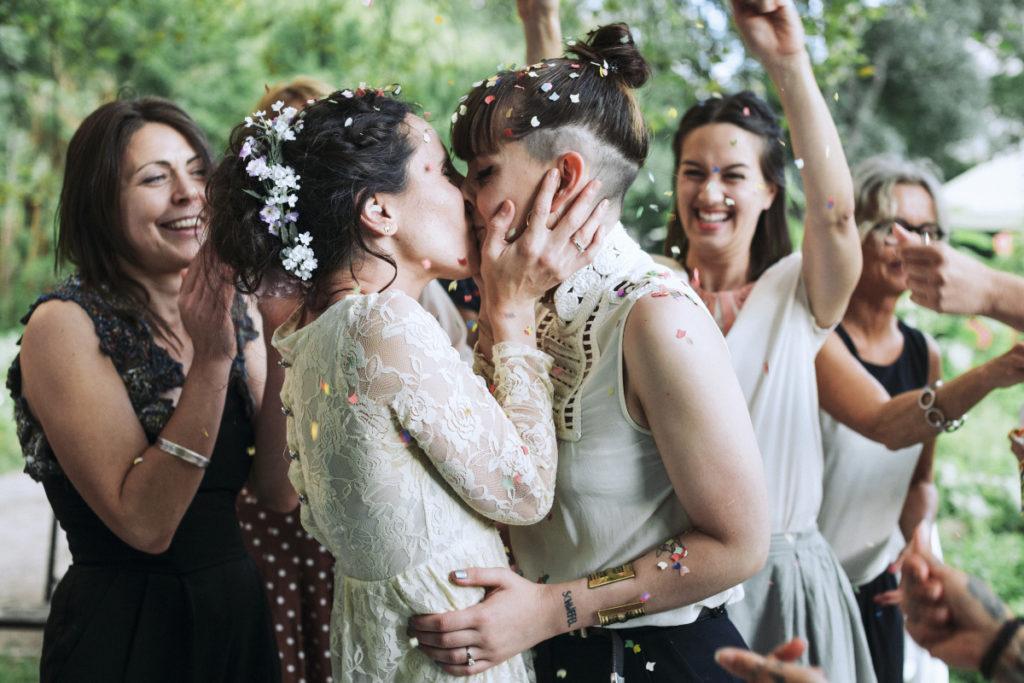 Lesbisches Brautpaar küssend, Freunde und Familie jubeln, werfen Kofetti