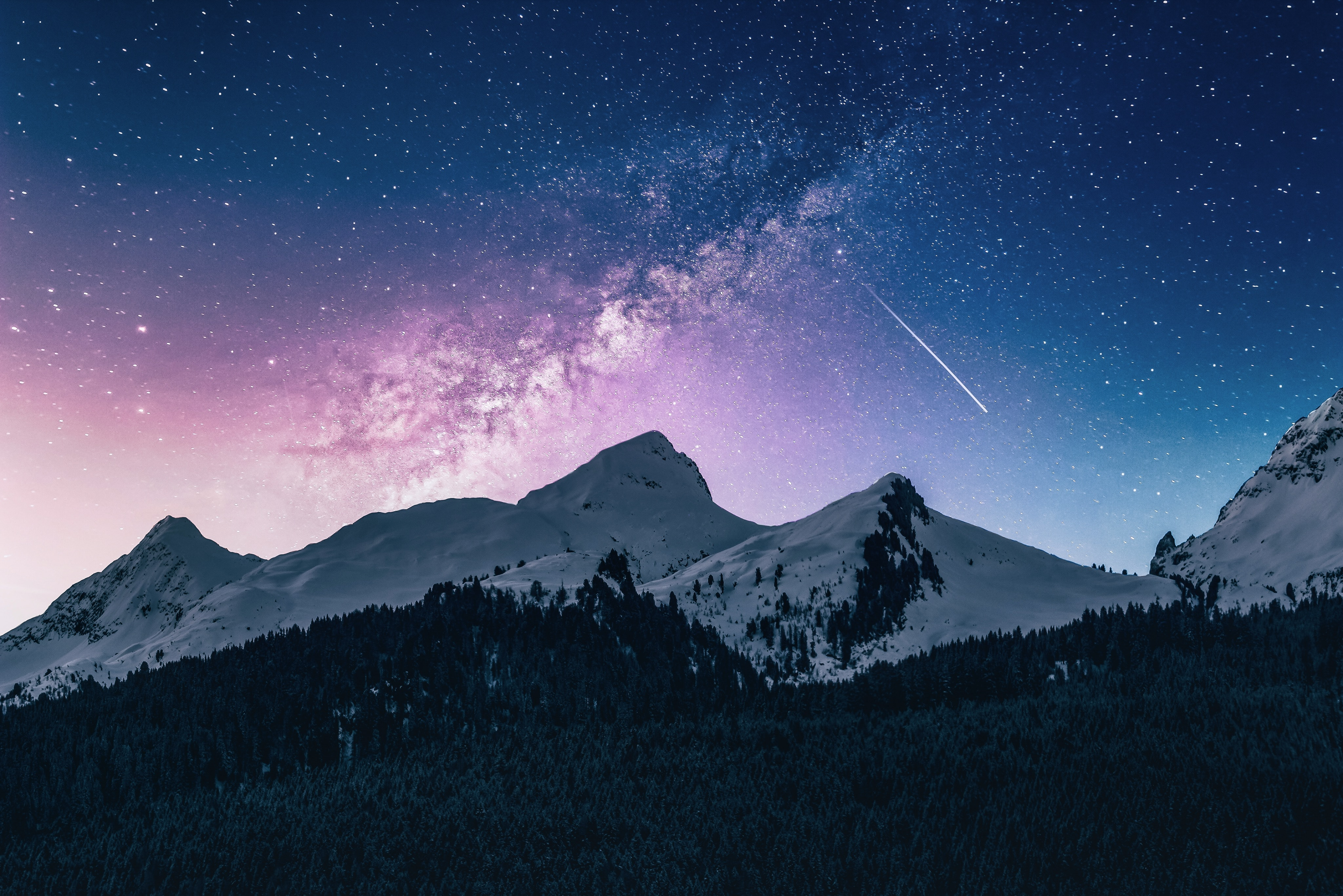 Ein Komet ist am Nachthimmel über den Bergen zu sehen.