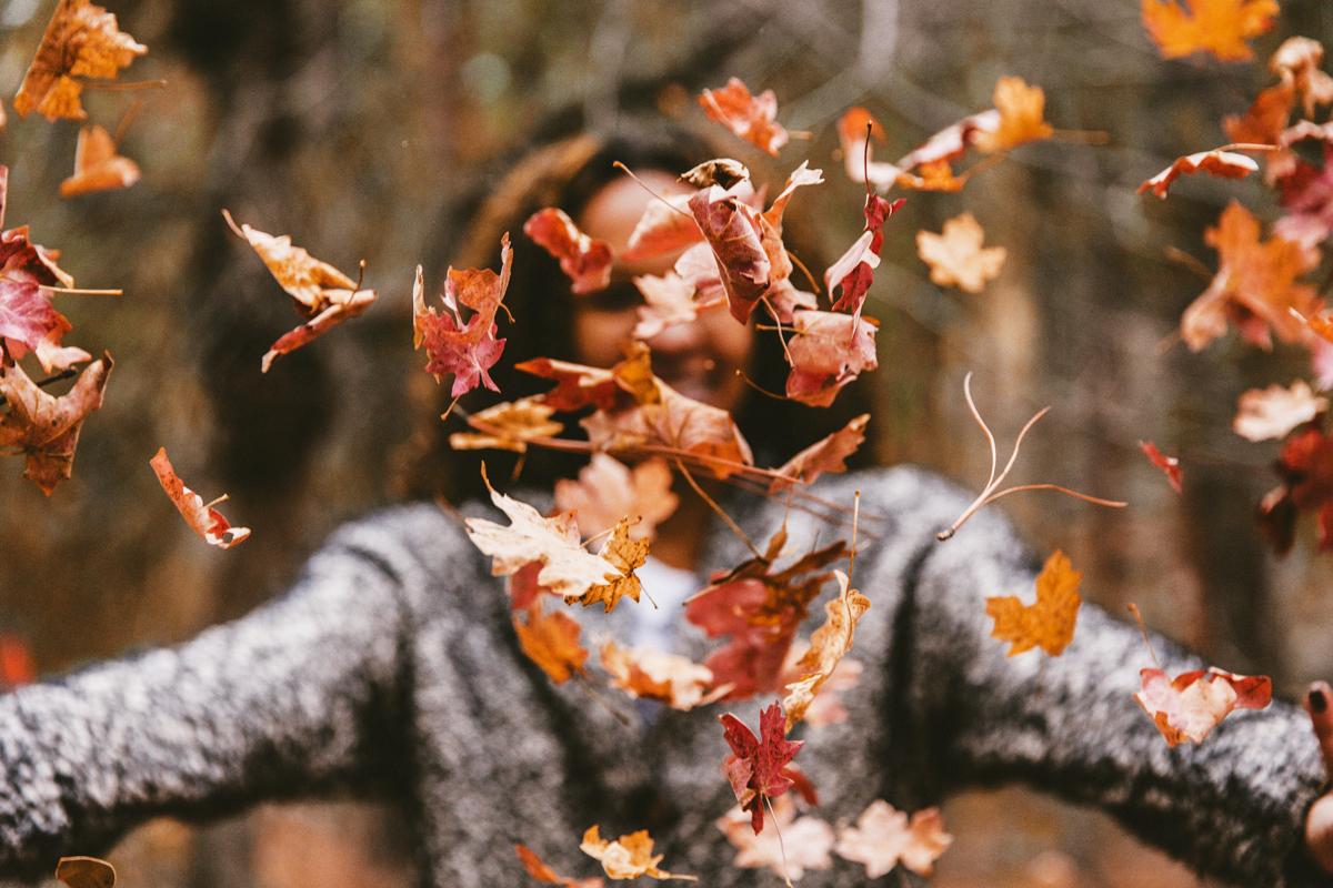 Frau wirft buntes Herbstlaub