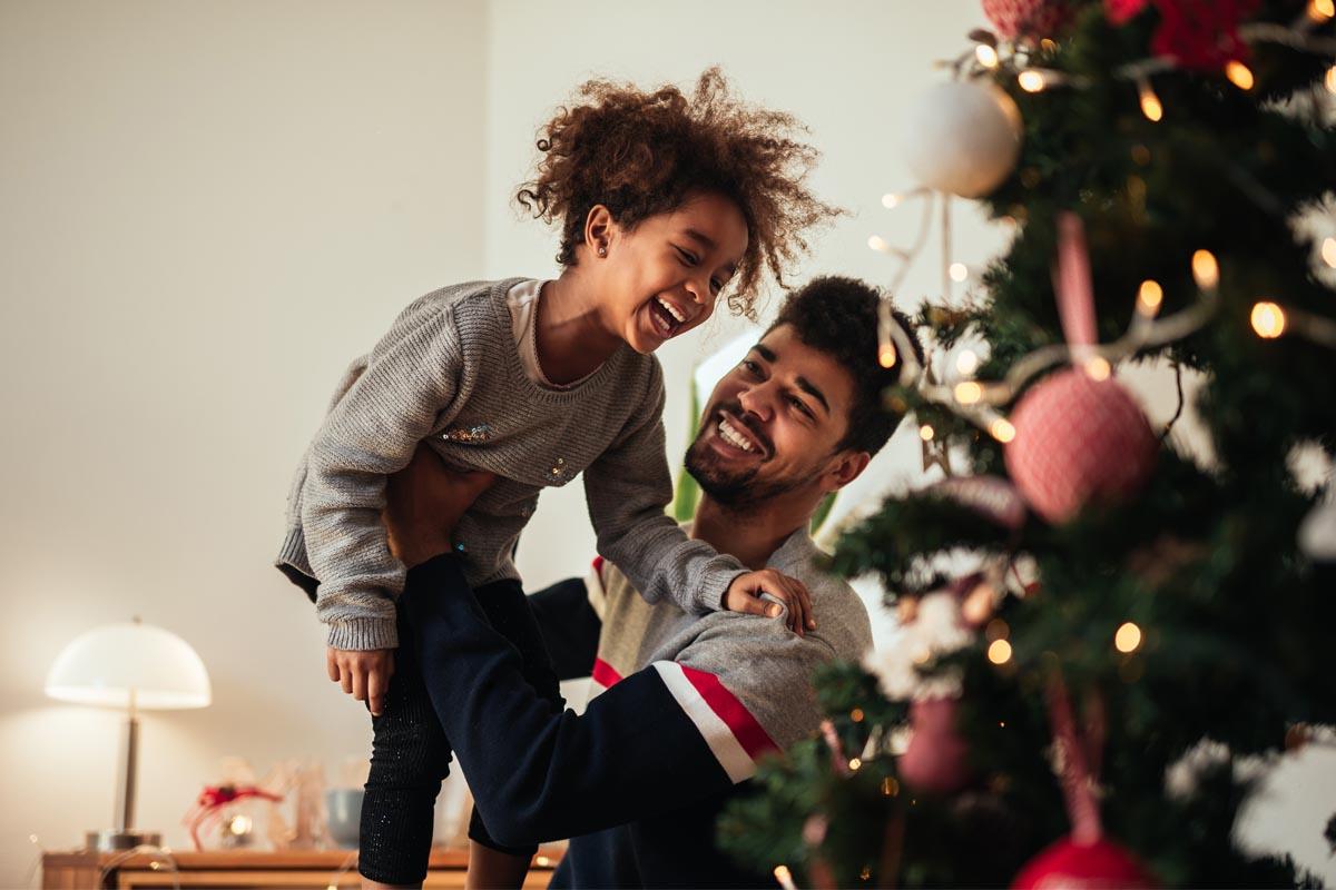 Der Vater hebt sein lachendes Kind in die Luft
