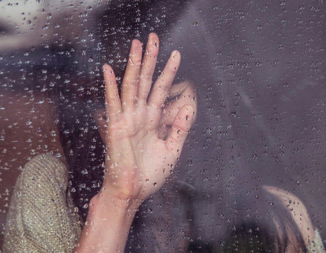 Eine Frau steht hinter einem mit Regentropfen benetztem Fenster. Dadurch entsteht ein toller Effekt.