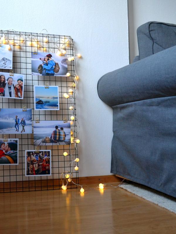 Metallgitter an die Wand gelehnt mit Fotoabzügen und Lichterkette dekoriert.