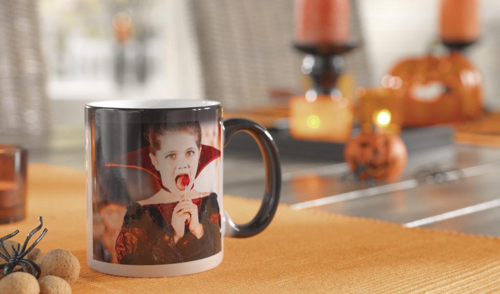Pixum Zaubertasse auf dem Halloween Tisch, auf der bei Wärme das Fotomotiv erscheint