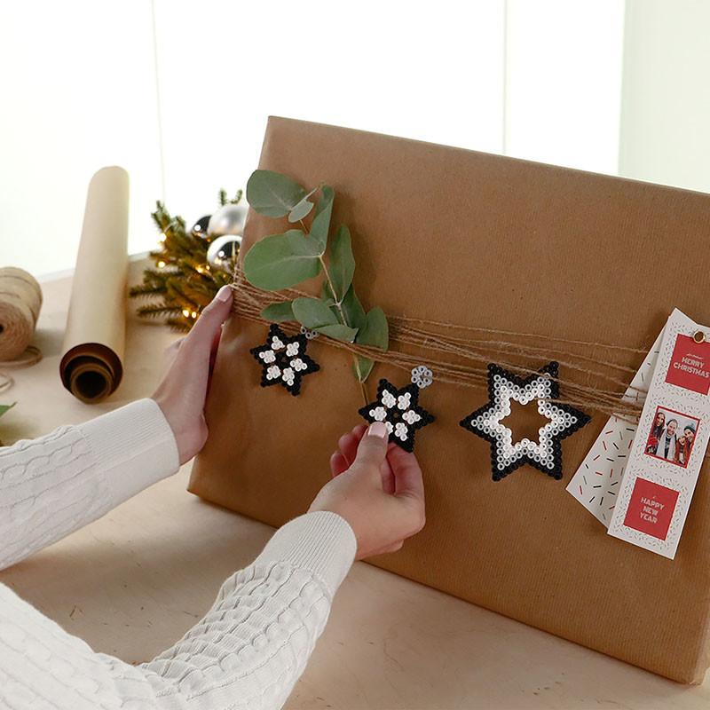 Neutral verpacktes Geschenk verziert mit Sternenanhängern, Eukalyptus und Fotostreifen