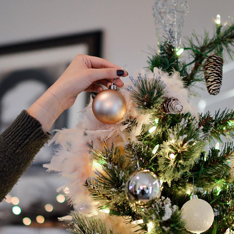 Weihnachtsbaum wird mit Federn, silbernen und weißen Kugeln geschmückt