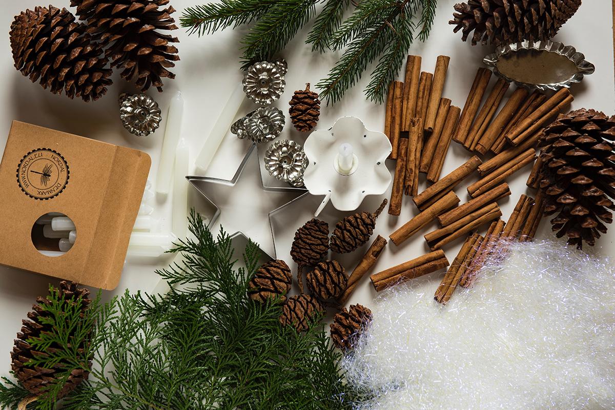 Zapfen, Zimtstangen, Kerzen und Kugeln auf weißem Hintergrund