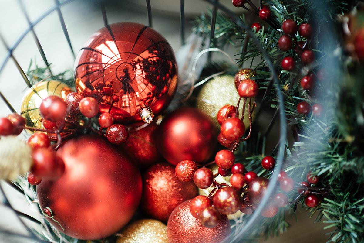 Verschieden große rote Weihnachtsbaumkugeln im Drahtkorb