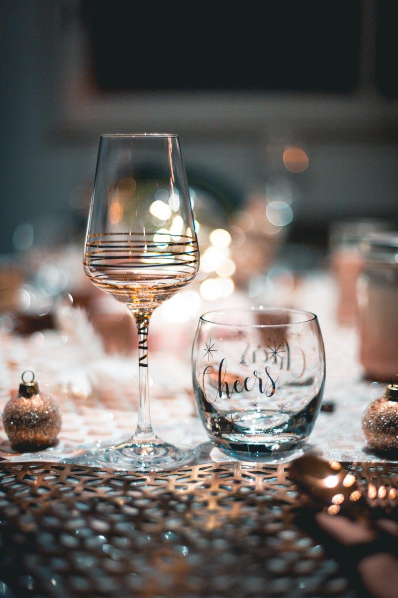 Ein Weinglas steht auf dem weihnachtlich geschmückten Tisch