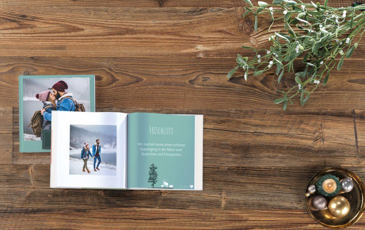 Gutschein Fotobuch auf einem Tisch mit einem Mistelzweig.