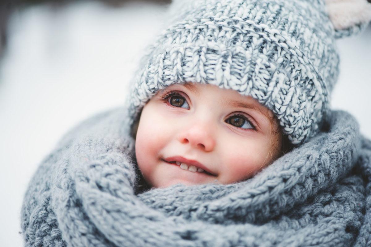 Mädchen steht verträumt im Schnee