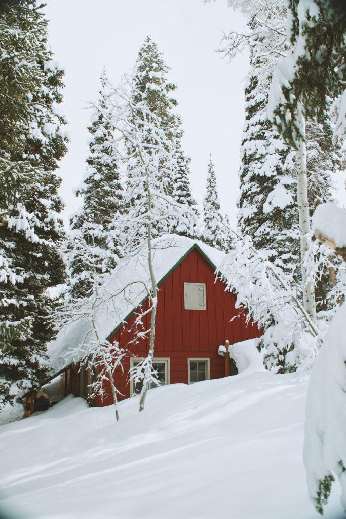 Rotes Holzhaus im verschneiten Wald