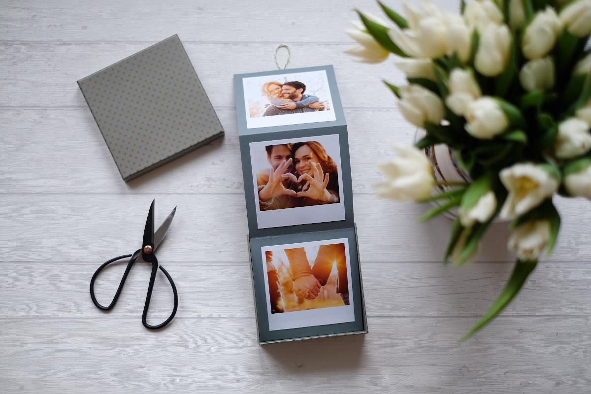 Papierstreifen zum Auseinanderklappen mit Fotoabzügen in einer Geschenkbox.