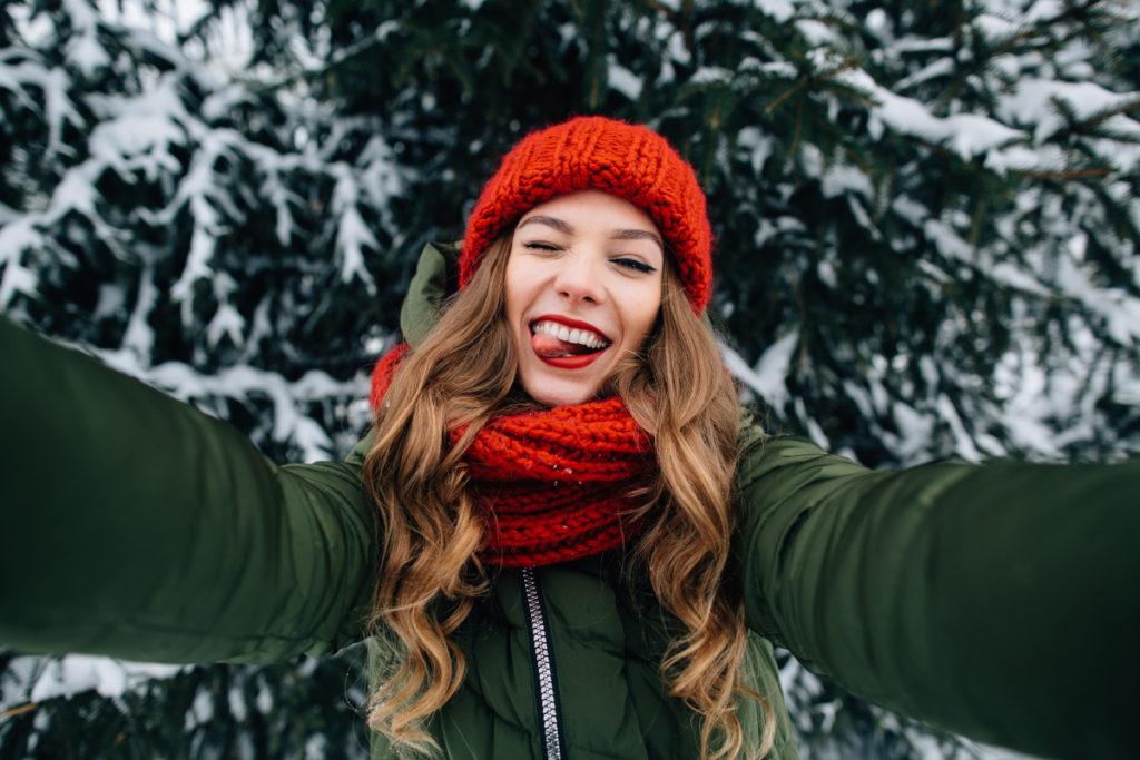 Frau vor verschneiter Tanne macht Selfie und streckt die Zunge raus