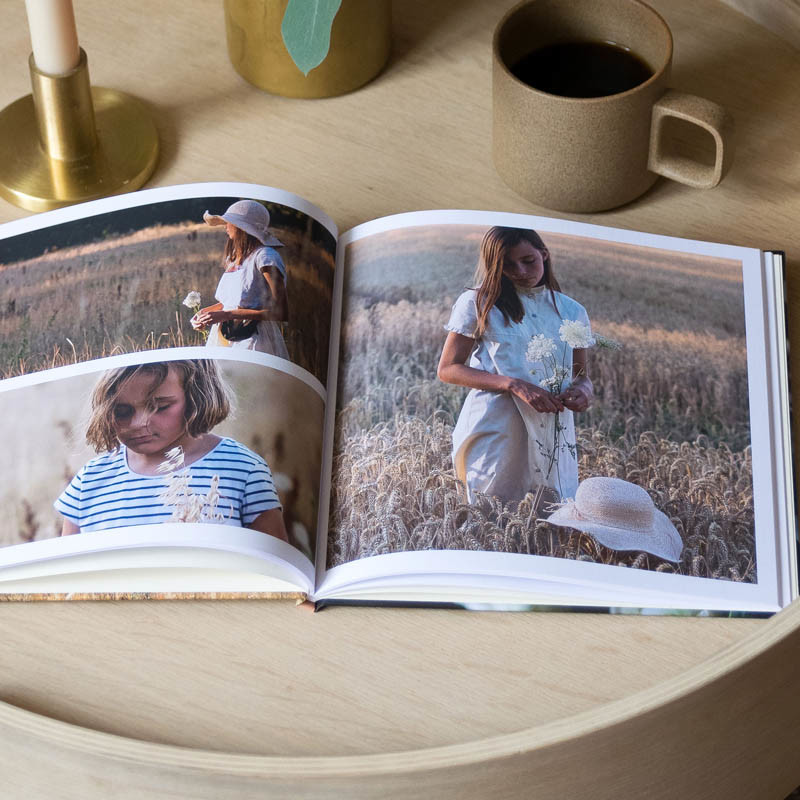 Fotobuch liegt aufgeklappt auf einem Beistelltisch aus Holz
