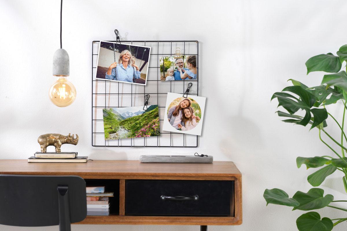 Fotogitter mit Fotoabzügen über einem Schreibtisch
