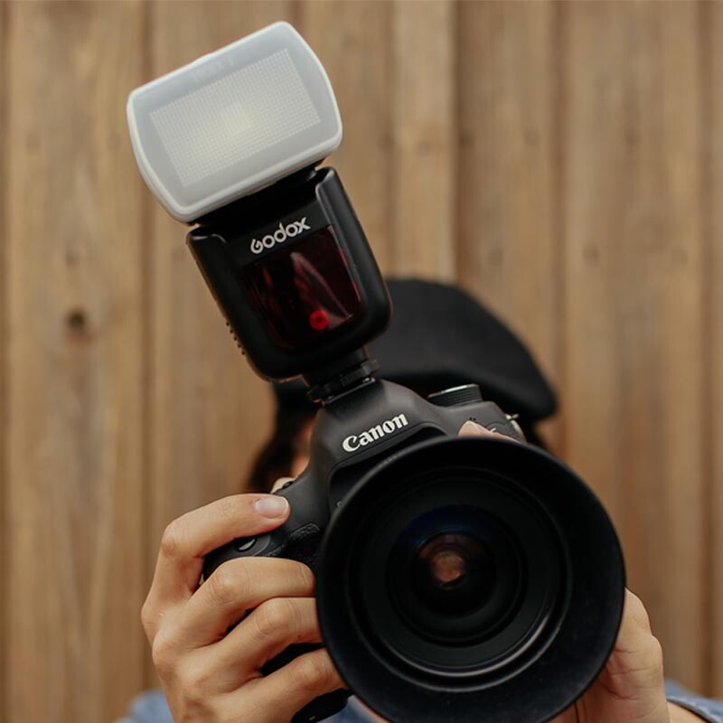 Mann hält eine Spiegelreflexkamera mit Aufsteckblitz vor sein Gesicht