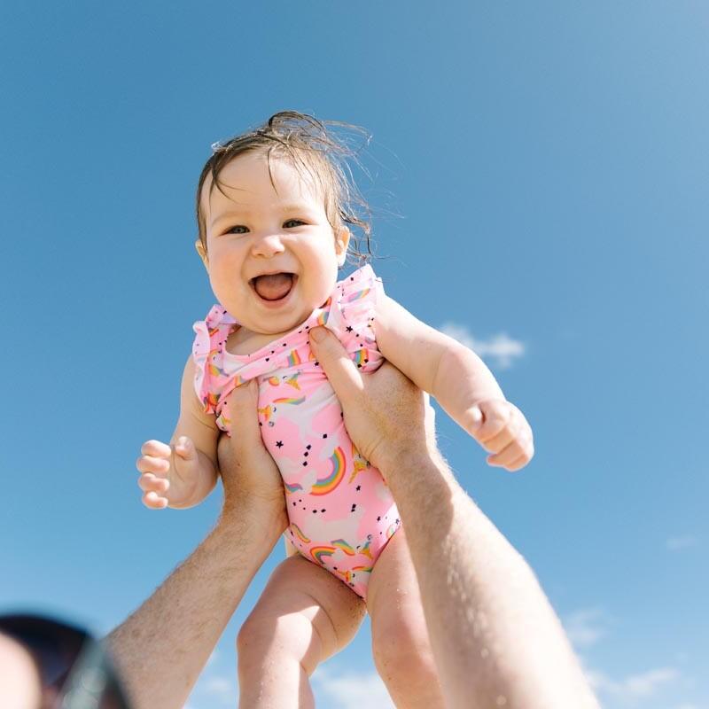 Vater hält sein Baby am Strand bei blauem Himmel und Sonnenschein in die Luft und bringt es so zum Lachen.