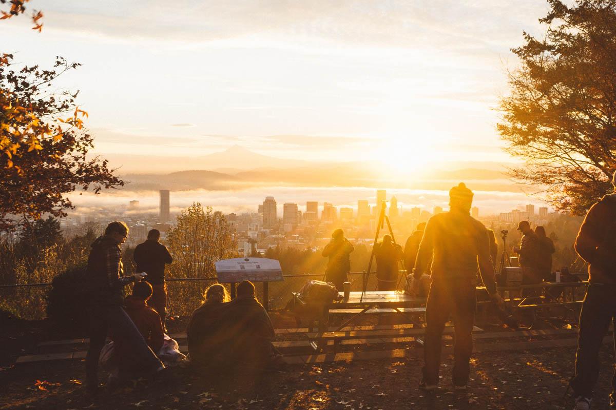 Menschen versammeln sich zum Sonnenuntergang an einem Aussichtspunkt mit Blick über die Stadt