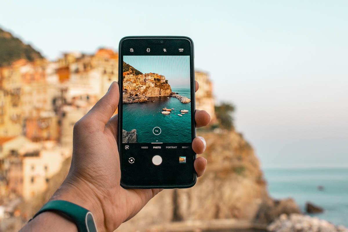 Mann fotografiert eine Küstenstand in Italien mit dem Smartphone