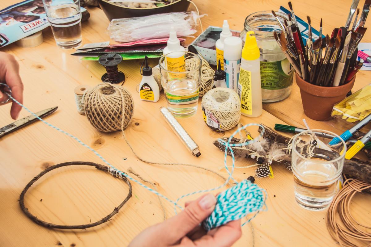 Basteltisch mit Klebern, Bändern und Pinseln