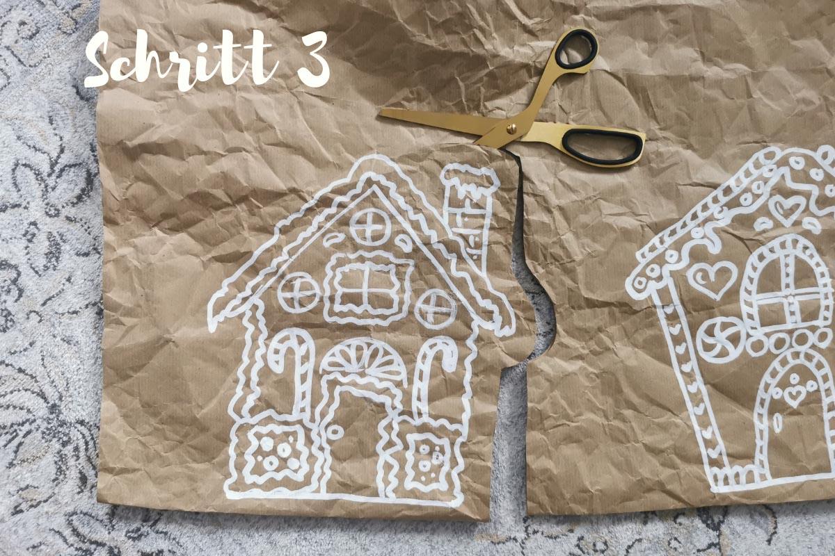 selbstgemalteLebkuchenhäuser auf Kraftpapier werden ausgeschnitten