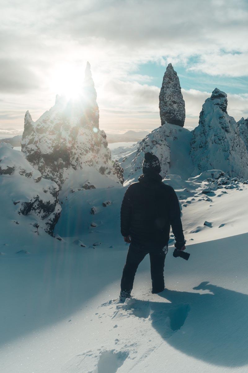 Mann steht im Tiefschnee mit Blick auf ein Bergpanorama