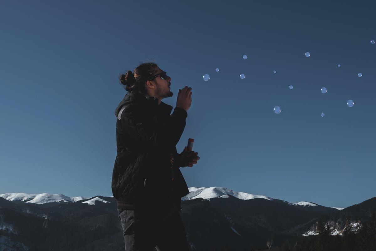 Mann pustet Seifenblasen in die Luft