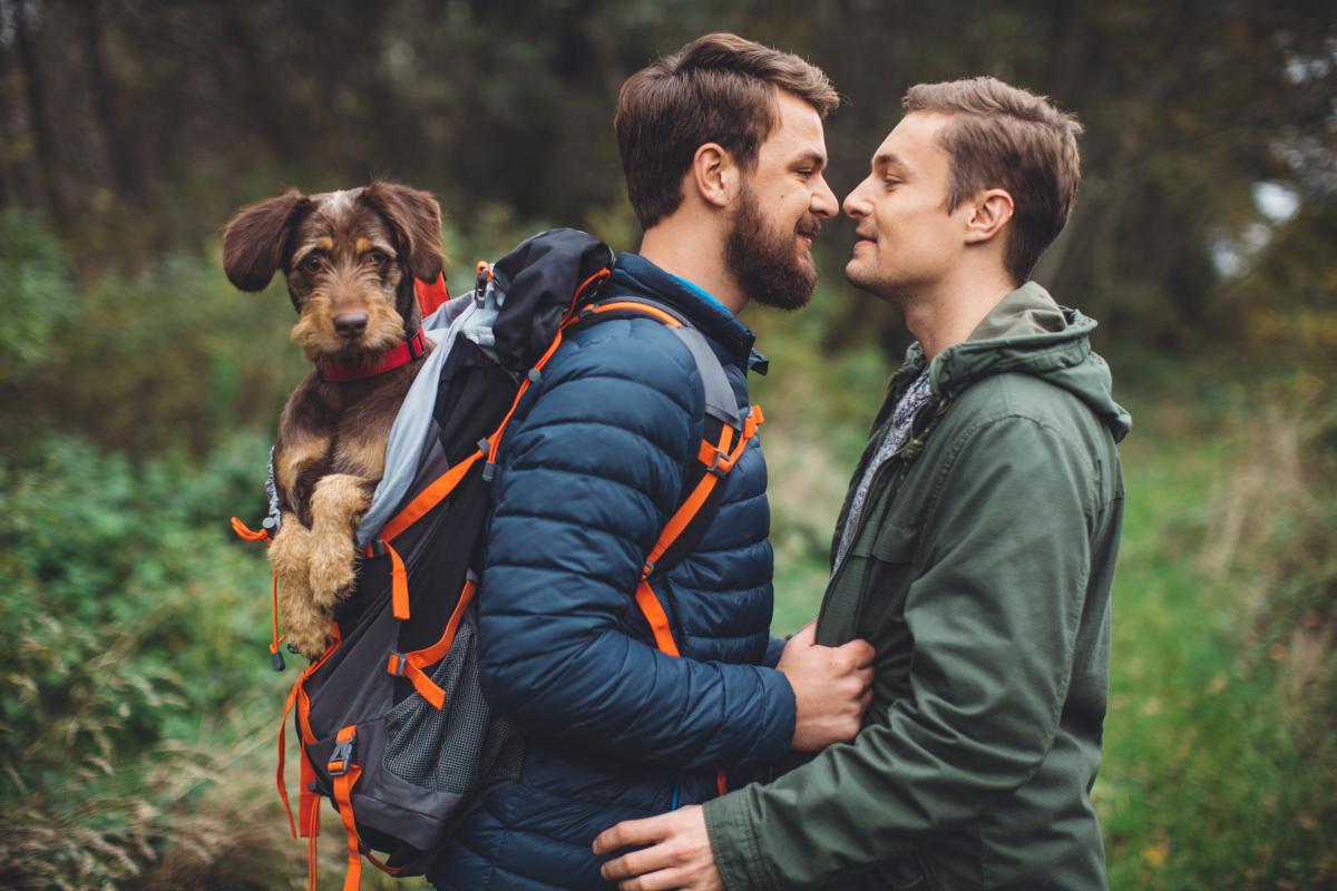 Schwules Paar mit Hund und Wanderkleidung