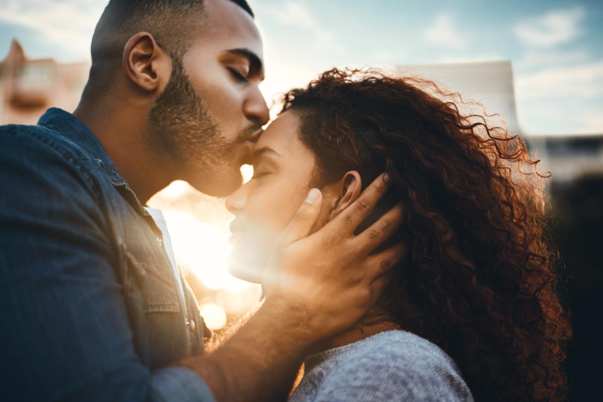 Mann küsst seine Partnerin auf die Stirn